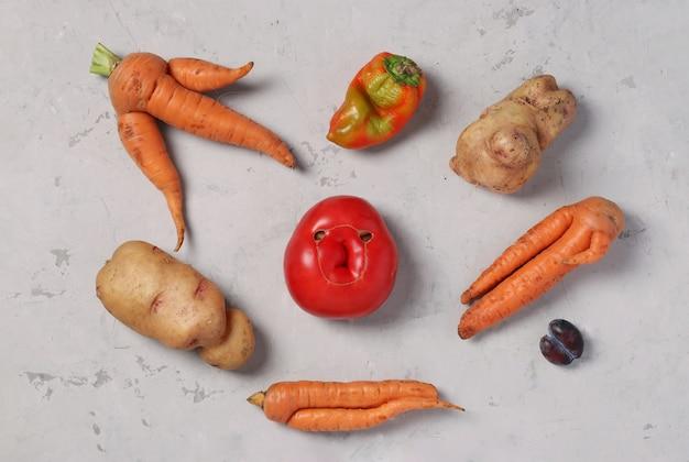 Trendy lelijke biologische groenten: aardappelen, wortelen, tomaat, paprika en pruimen op grijze achtergrond, lelijk voedselconcept, van bovenaf bekijken