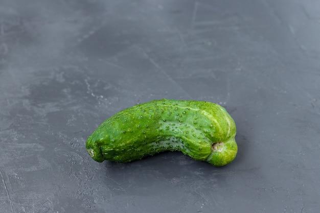 Trendy lelijke biologische komkommer op een grijze donkere achtergrond