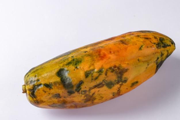 Trendy lelijke biologische papaja op witte achtergrond, horizontale oriëntatie