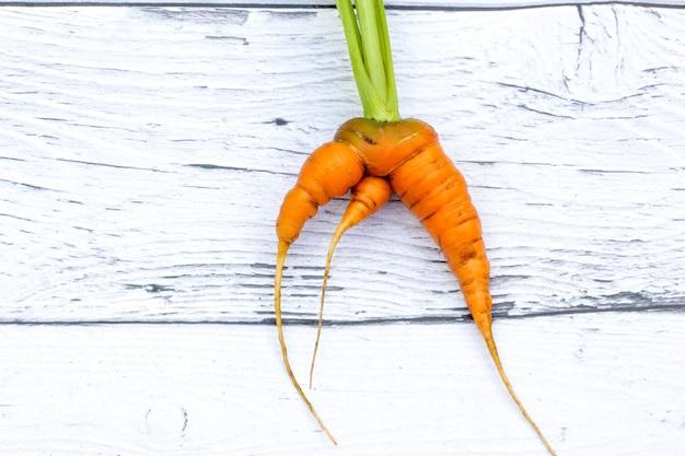 Trendy lelijke biologische plantaardige rode wortel op de houten achtergrond grappige misvormde ongewone groente