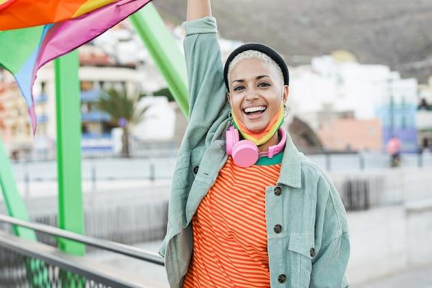 Trendy lesbische vrouw die lgbt-regenboogvlag vasthoudt tijdens de gay pride-parade terwijl ze een veiligheidsmasker onder de kin draagt voor een uitbraak van het coronavirus