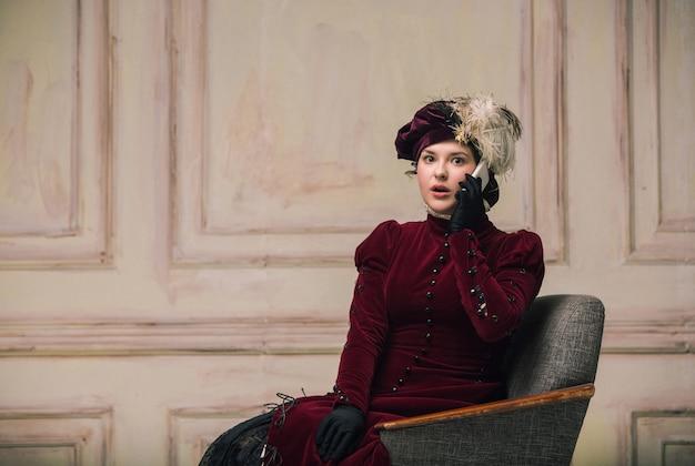 Trendy look vrouw portret van renaissance periode met smartphone