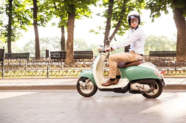 Trendy man een scooter rijden in de helm