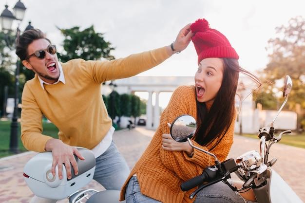 Trendy man met baard die een grapje maakt met een vriend die haar rode hoed vasthoudt