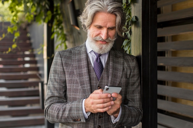 Trendy man met baard mobiele telefoon browsen