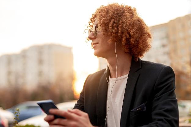 Trendy man met smartphone en koptelefoon rusten op straat
