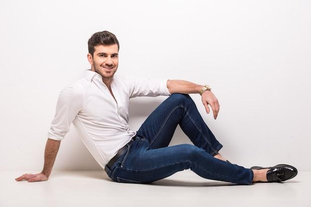 Trendy man zit op de vloer