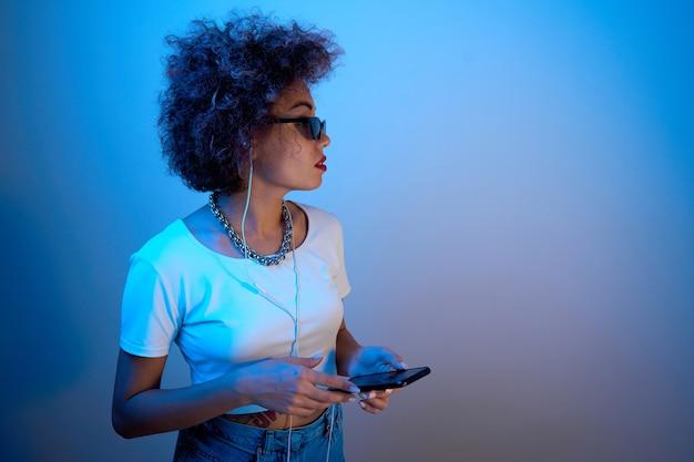 Trendy meisje met afro-krullen gebruikt een smartphone en koptelefoon op een studioachtergrond met kopieerruimte