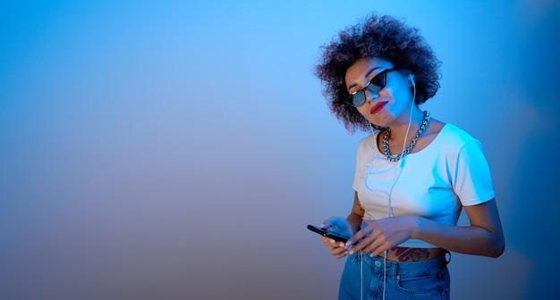 Trendy meisje met afro-krullen luistert en geniet van muziek met een koptelefoon in blauw neonlicht, hiphopmodel danst en ontspant