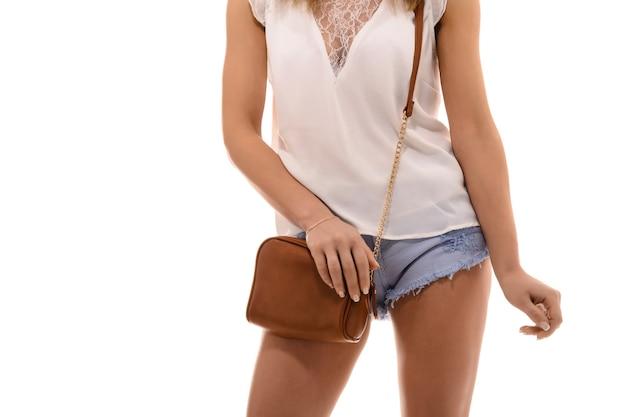 Trendy meisje met kleine bruine leren tas handtas in de hand stijlvolle accessoires