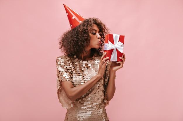 Trendy meisje met kort donkerbruin kapsel in beige glanzende jurk en vakantiepet die haar rode geschenkdoos kust op geïsoleerde muur..
