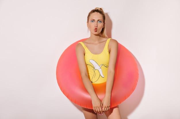 Trendy meisje met lichte make-up in een geel zwempak met bananenpatroon dat naar de camera kijkt en een grote roze zwemring op de witte muur