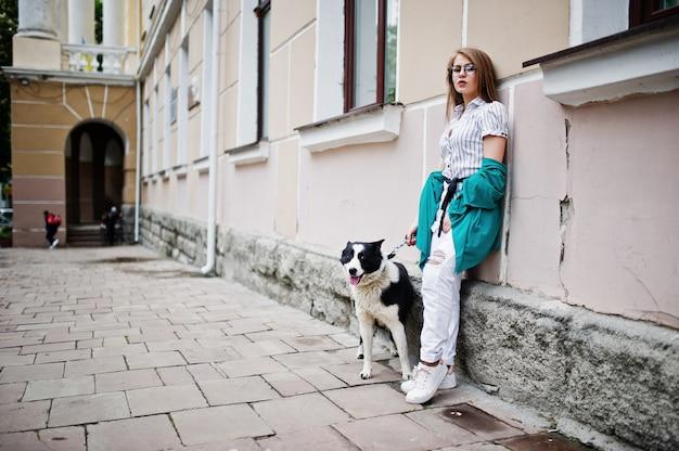 Trendy meisje op bril en gescheurde spijkerbroek met russisch-europese laika (husky) hond aan de leiband, tegen straat van de stad
