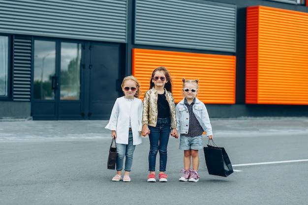 Trendy meisjes in zonnebril met zakken in hun handen die dichtbij de winkel stellen. winkelen en stedelijke levensstijl concept