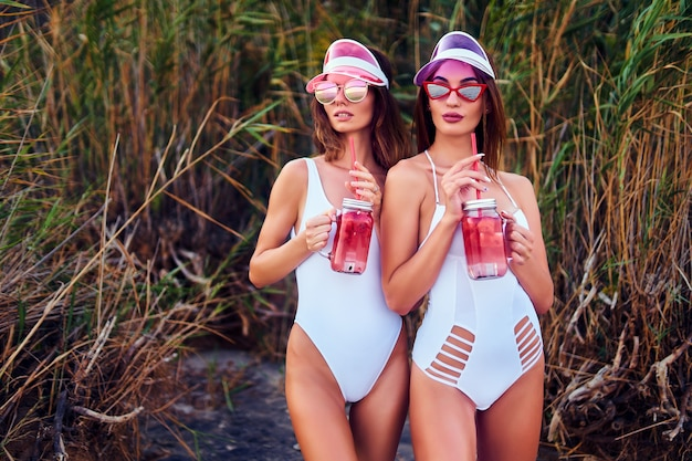 Trendy meisjes in zwempakken die limonades houden