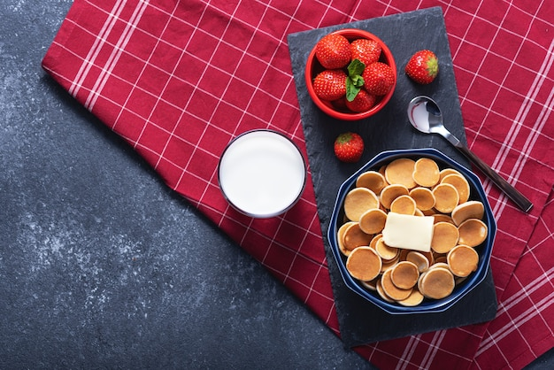 Trendy minigraanpannekoeken in blauwe kom met beboterende toast, aardbeien, lepel, glas melk op grijs