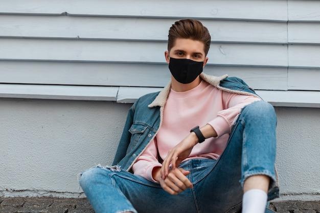 Trendy model jongeman in stijlvol spijkerjasje in gescheurde modieuze spijkerbroek in mode zwart masker zit op stenen tegel in de buurt van vintage muur in de stad. aantrekkelijke man in trendy casual kleding op straat.