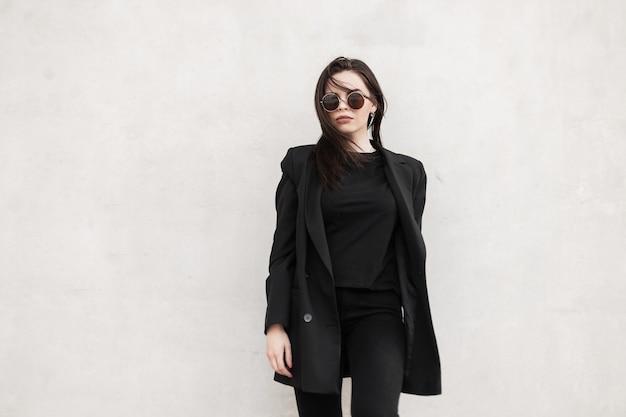 Trendy model prachtige jonge vrouw in coole spiegelzonnebril in modieuze zwarte casual jas in stijlvol t-shirt in de buurt van moderne witte muur in de stad. stedelijke sexy meisje in mode jeugd outfit in straat.