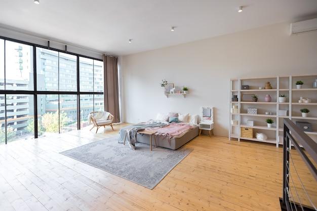 Trendy modern design appartement op twee niveaus met grote hoge ramen. de stijlvolle woonkamer en keuken in lichte kleurstelling worden ontkleed door een glazen wand. slaapkamer op de tweede verdieping.