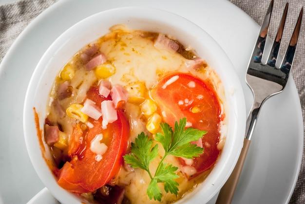 Trendy modern eten, fast food, lunch in de magnetron. pizza in een mok, met ham, tomaten, champignons, kaas. witte kop, met een vork, op een witte marmeren tafel. copyspace bovenaanzicht