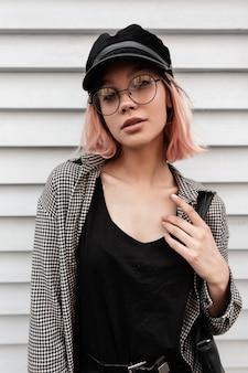 Trendy modieuze jonge hipster meisje in stijlvolle kleding met mode ronde bril, vintage hoed en tas staat in de buurt van een houten vintage huis