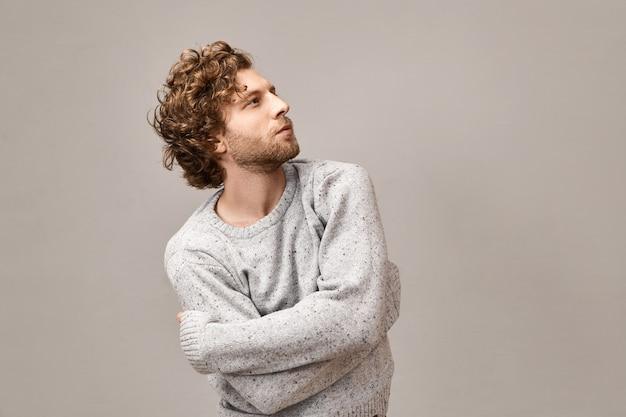 Trendy modieuze jonge hipster met getrimde baard, golvende roodachtige en ideale gezichtskenmerken opkijken met een peinzende uitdrukking in een oversized stijlvolle pullover, met gekruiste armen op zijn borst
