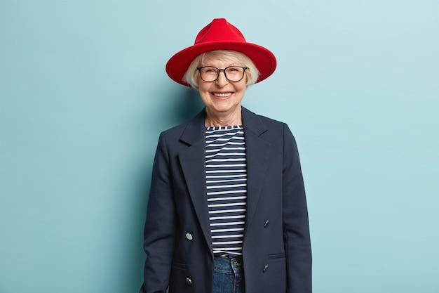 Trendy modieuze oudere vrouw lacht vrolijk, vertoont witte tanden, heeft een gerimpelde huid, gekleed in stijlvolle formele kleding, in goed humeur, klaar voor werk, geniet van een mooie dag, geïsoleerd op blauwe muur