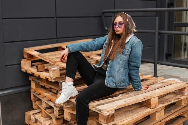 Trendy mooie jonge vrouw hipster in violet zonnebril in militaire kap in fashion denim jasje in jeans in witte leren laarzen ontspant op houten pallets in de stad. modern meisjesmodel buitenshuis.