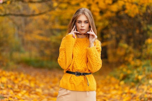 Trendy mooie mode jonge vrouw in gebreide vintage gele trui jurken zonnebril buitenshuis op gouden herfst gebladerte achtergrond