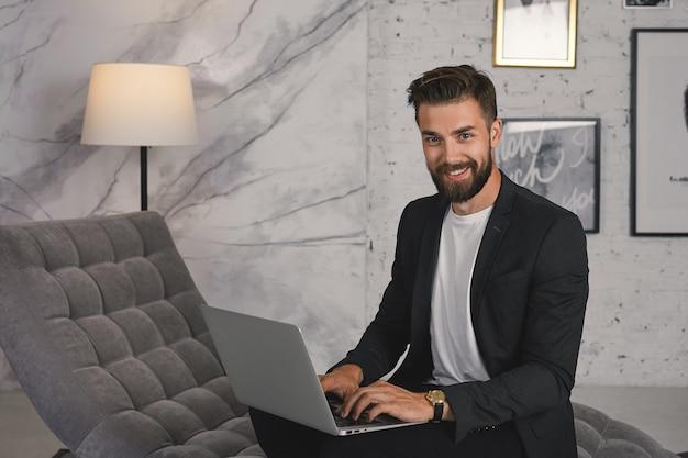 Trendy ogende positieve jonge ongeschoren mannelijke werknemer gekleed in stijlvolle luxe kleding met behulp van generieke laptopcomputer op sofa in moderne kantoren, vreugde over succes, breed glimlachend