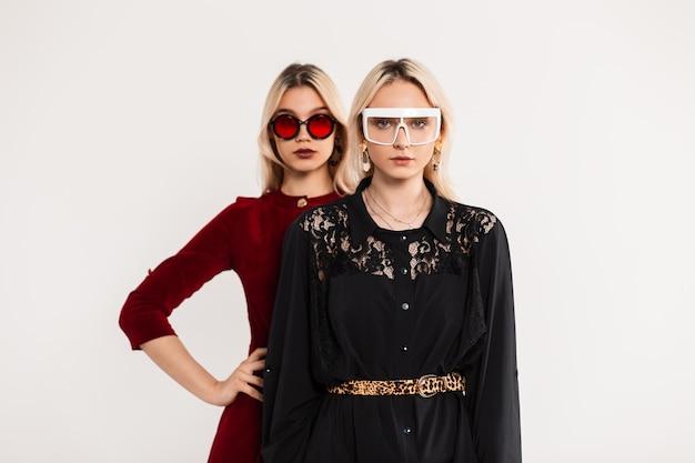 Trendy portret twee blonde vriendinnen in modieuze gekleurde jeugdbril in rode en zwarte jurken in de buurt van grijze vintage muur
