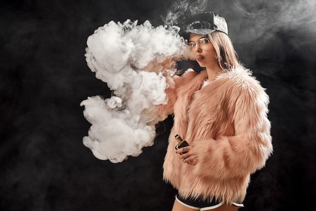 Trendy rap vrouw in roze bontjas en caping op zwart