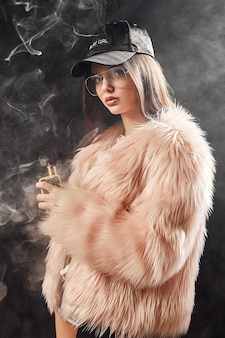 Trendy rapvrouw in roze bontjas en vapen op zwart