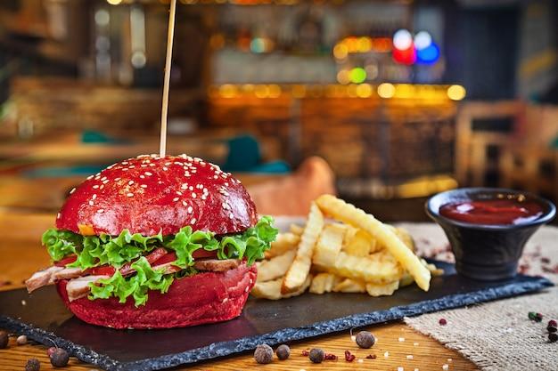 Trendy rode bolburger met varkensvlees geserveerd met frietjes en rode saus. ongezond fastfood. hamburger in restaurant interieur. amerikaanse hamburger op stenen plaat en loft hebben met kopie ruimte. belegd broodje