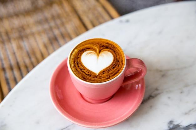 Trendy roze kop warme cappuccino op marmeren tafelondergrond. hartvorm latte art voor symbool van liefde. een kopje voor de ochtendroutine.