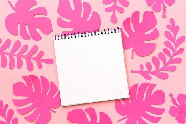 Trendy roze tropische bladeren van papier en notitieblok openen op roze achtergrond, creatieve papier kunst