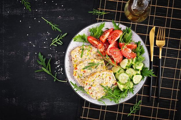 Trendy salade. kippengehaktbrood met salade verse tomaten en komkommer. gezonde voeding, ketogeen dieet, dieetlunchconcept. keto, paleo-dieetmenu. bovenaanzicht, boven het hoofd, plat gelegd