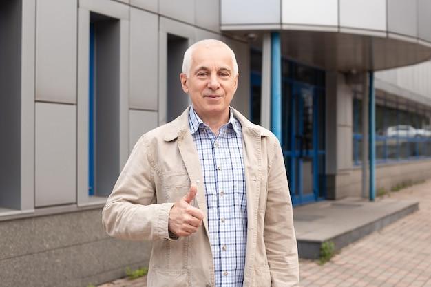 Trendy senior man duimen opdagen buiten in stad landschap in de buurt van kantoorgebouwen
