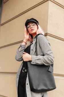 Trendy serieuze glamoureuze mooie jonge vrouw model met bril en een vintage pet in een modieus shirt en jeans met een zwarte tas wandelingen in de stad