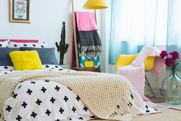 Trendy slaapkamer met kleurrijk beddengoed, dekens en combinatie van materialen