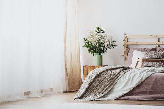 Trendy slaapkamerinterieur met comfortabel bed met vuil roze beddengoed en beige warme deken, echte foto met kopieerruimte