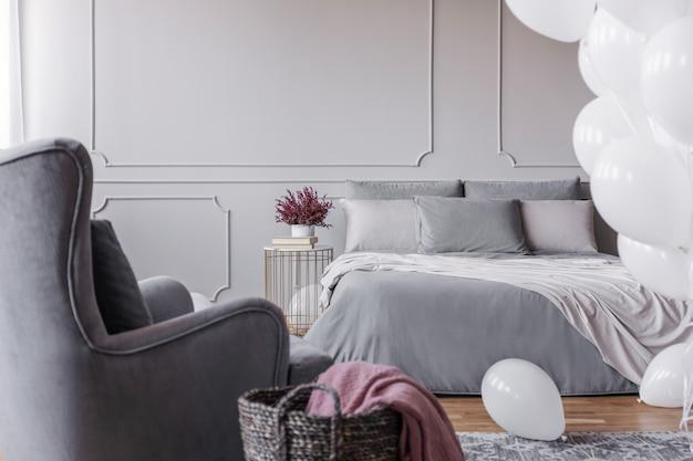 Trendy slaapkamerontwerp met elegant tweepersoonsbed met grijze lakens, comfortabele fauteuil en heide op nachtkastje, echte foto met kopieerruimte op lege grijze muur