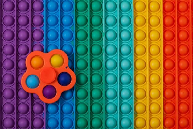 Trendy speelgoedspinner simple dimple op veelkleurig oppervlak pop it. tik op bubbel, vingerspel.
