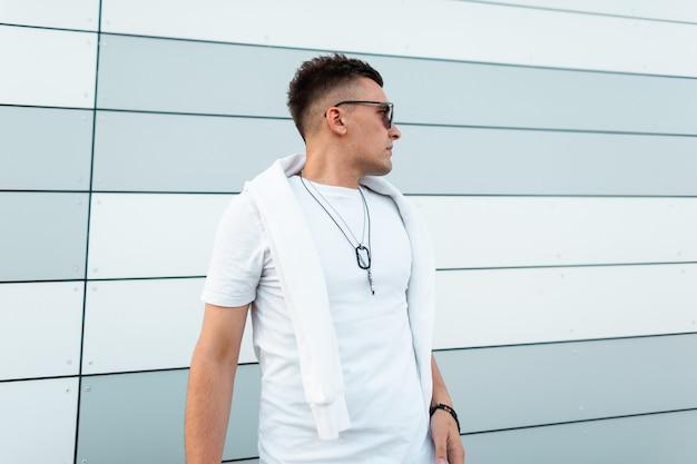 Trendy stedelijk mannenmodel in stijlvolle zwarte zonnebril in een wit trendy t-shirt staat bij een moderne muur in de stad.