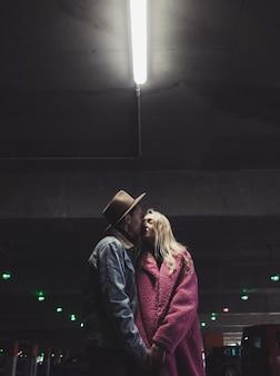 Trendy stijlvol paar omhelst in een donkere garage