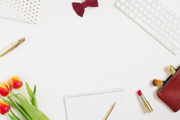 Trendy thuiswerkplek. kantoor aan huis bureau met laptop, notebook, tulp, pen, accessoires en cosmetica op witte achtergrond.