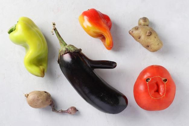 Trendy ugly organic vegetables: aardappelen, paprika, aubergine en tomaat op grijze achtergrond, lelijk voedselconcept, horizontaal formaat, weergave van bovenaf