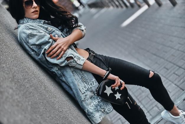 Trendy uitstraling. mooie jonge vrouw in denim jasje camera kijken
