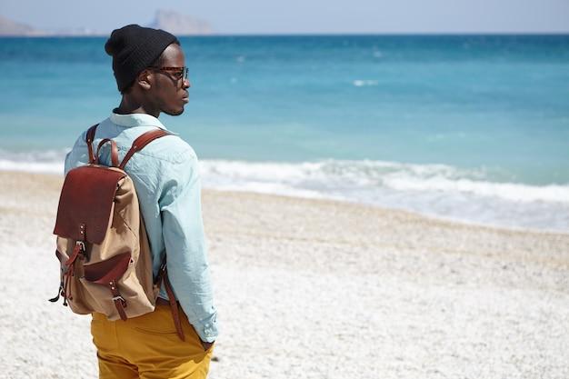 Trendy uitziende jonge afro-amerikaanse reiziger die een knapzak draagt die naar de kalme azuurblauwe zee voor hem kijkt, met een bedachtzame dromerige uitdrukking, staande op een kiezelstrand