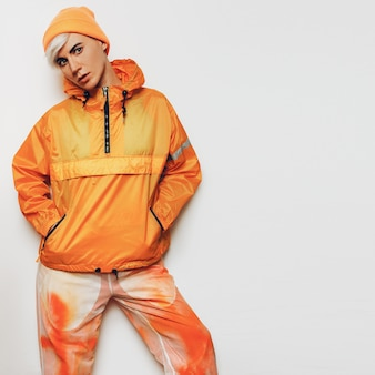 Trendy urban outfit tomboy meisje in een fel oranje sportkleding